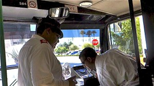 Driver Rick Hernandez and Dan Solomon are seen in the cab of their bus making final arrangements for another tour.  Photo by Diane Taylor